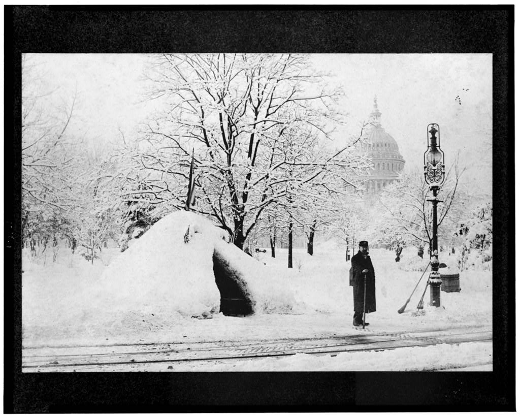 Man standing by snow hut, after blizzard of 1888, with U.S. Capitol in background, Washington, D.C.
